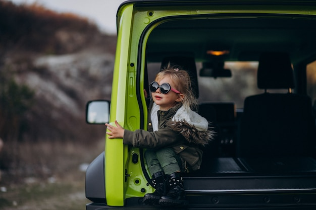 Маленькая милая девочка сидит в задней части автомобиля