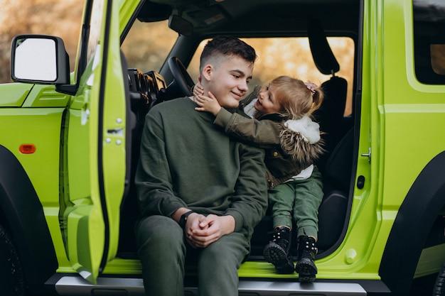 Брат с сестренкой сидят в зеленой машине