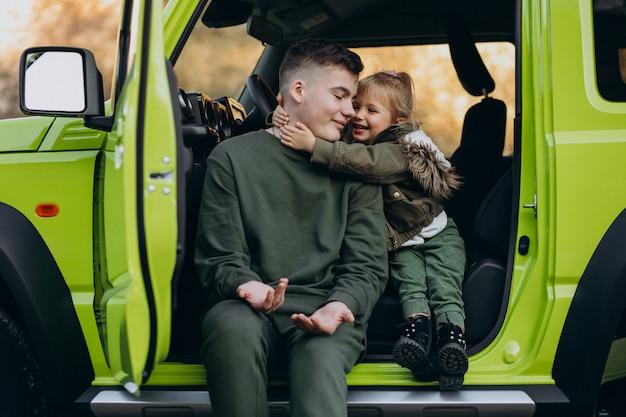 緑の車に座っている妹と弟