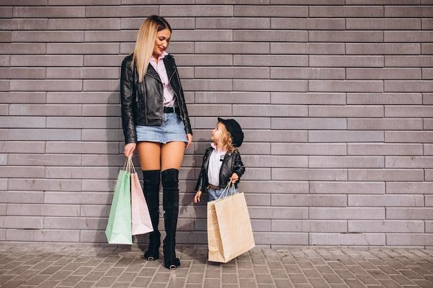 買い物袋と小さなかわいい娘を持つ母