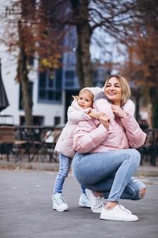 Мать с маленькой дочкой на улице в теплой одежде
