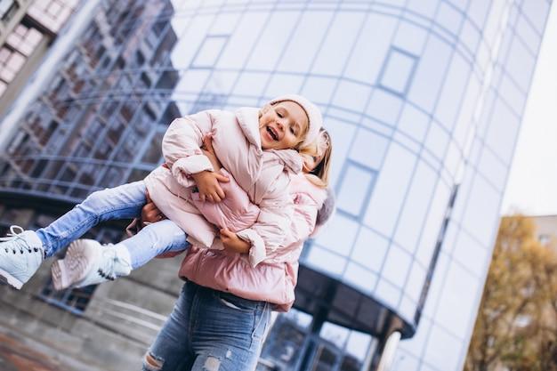 通りの外で暖かい布に身を包んだ彼女の小さな娘を持つ母
