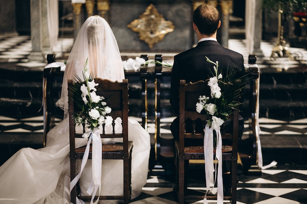 結婚式の日に椅子に座っている新郎新婦、後ろから