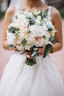 Невеста держит свой букет в день своей свадьбы