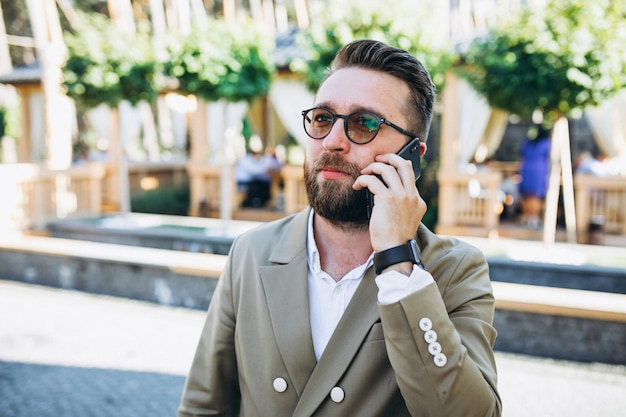 電話を使用して若いハンサムなビジネス男