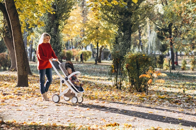 秋の公園を歩いて赤ん坊の娘を持つ若い母親