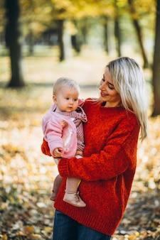 秋の公園で彼女の赤ん坊の娘を持つ母