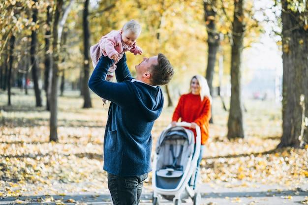 Семья с дочерью гуляет в осеннем парке