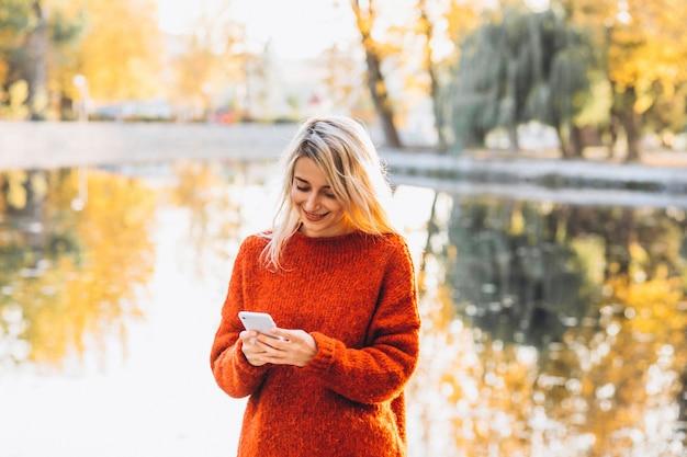 湖のそばの公園で携帯電話を使用して若い女性