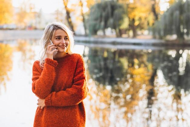 Молодая женщина, с помощью телефона в парке у озера