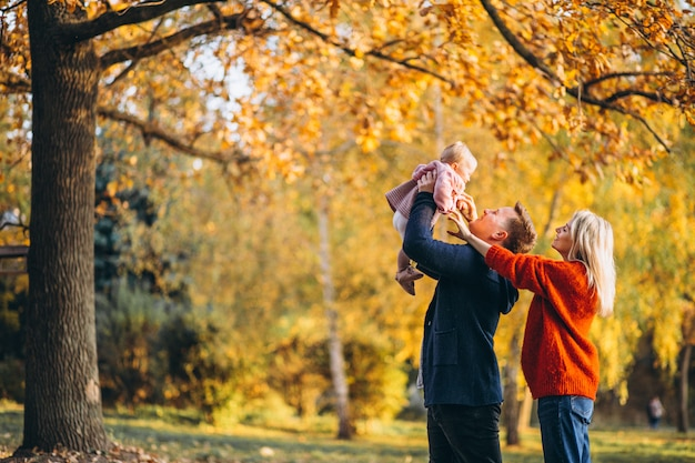 Семья с маленькой дочкой гуляет в осеннем парке