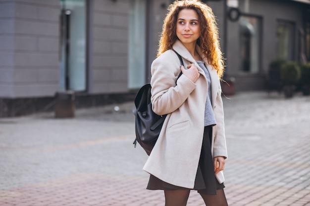 秋のコートを歩いて巻き毛のきれいな女性