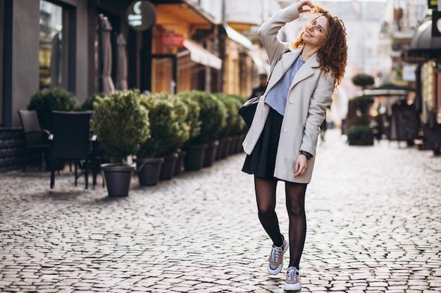Красивая женщина с вьющимися волосами, прогулки на улице кафе