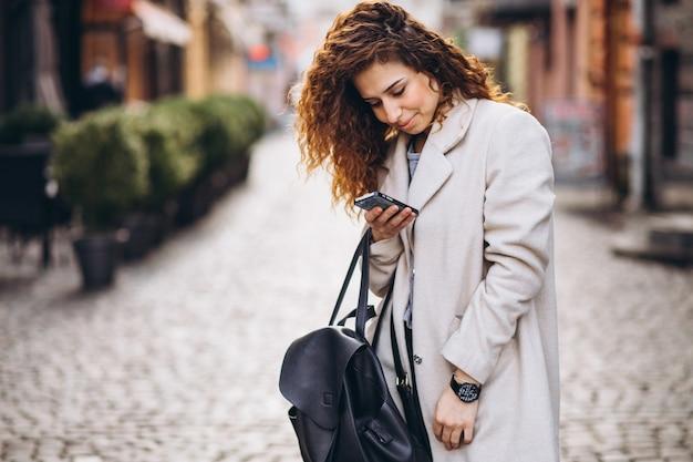 Молодая женщина с вьющимися волосами, с помощью телефона на улице