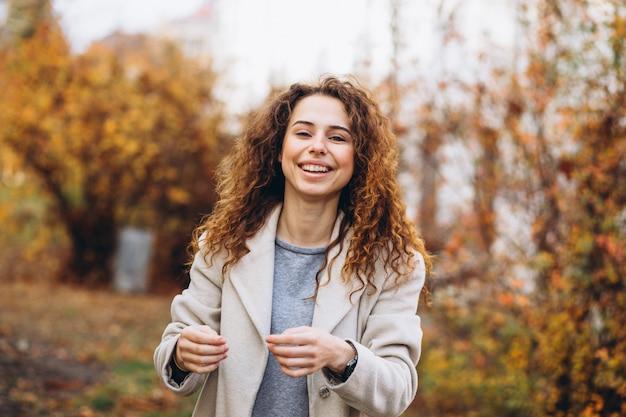 Молодая женщина с вьющимися волосами в парке