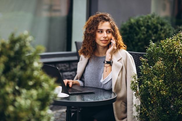 Молодая коммерсантка работая на компьютере вне кафе