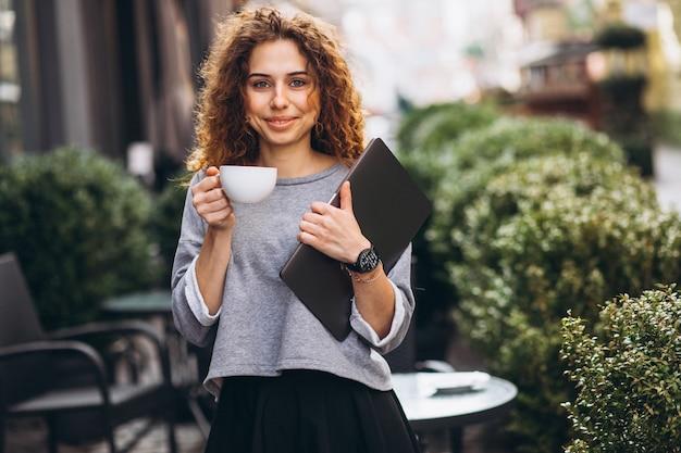ラップトップを保持しているカフェの外でコーヒーを飲む若い実業家
