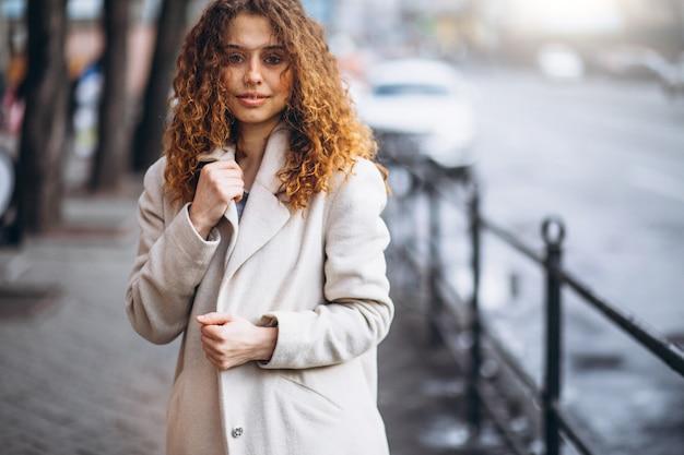 通りの外の巻き毛を持つ若い女性