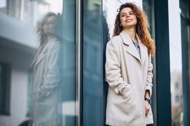 Молодая женщина с вьющимися волосами за пределами улицы