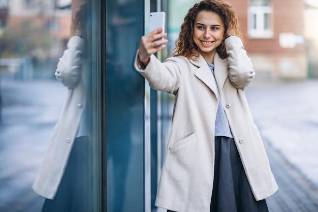 通りで電話を使用して巻き毛を持つ若い女性