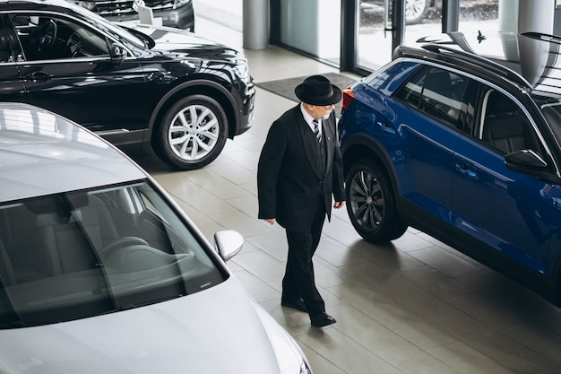 Старший мужчина в автосалоне, выбирая автомобиль