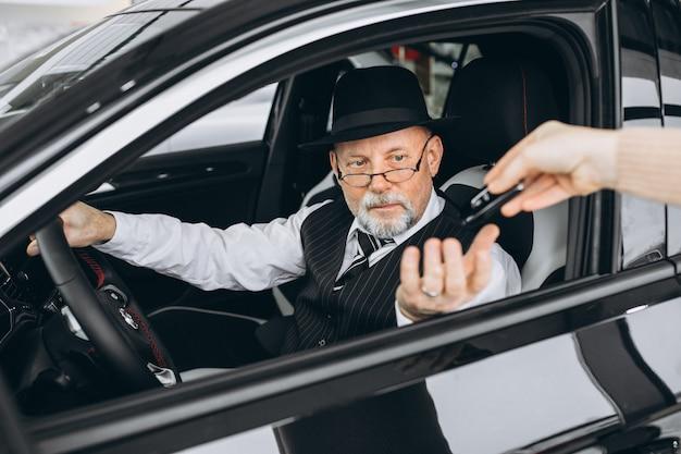 Старший мужчина сидит в машине