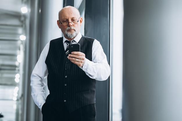 Старший бизнесмен разговаривает по телефону в офисе