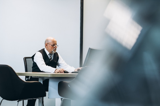 Старший менеджер в офисе работает за компьютером