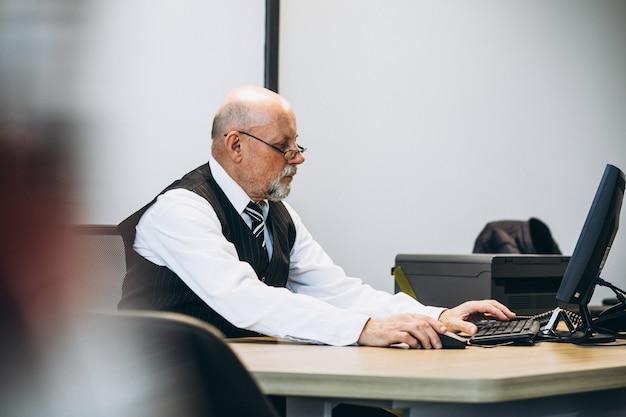 コンピューターに取り組んでいるオフィスでシニアマネージャー