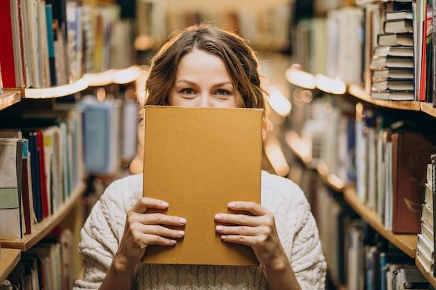 Молодая женщина учится в библиотеке