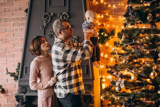 父の母と幼い息子がクリスマスツリーを飾る