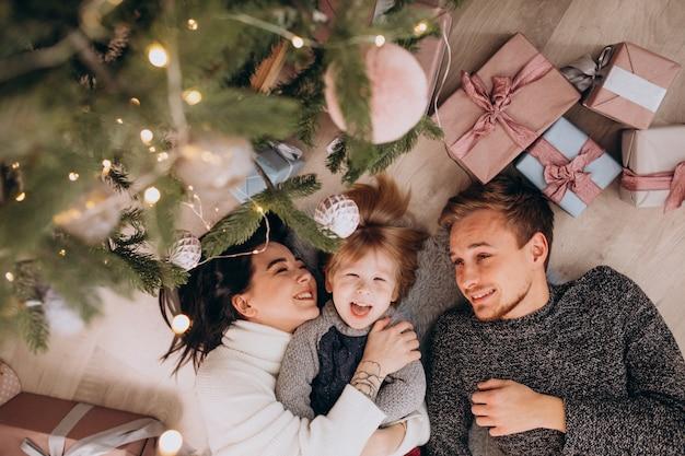 クリスマスツリーの下の幼い息子と若い家族