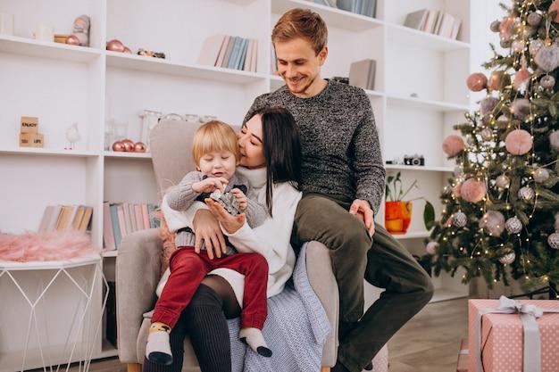 クリスマスツリーの贈り物を開梱して座っている幼い息子を持つ若い家族