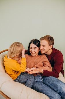 椅子に座っている幼い息子を持つ若い家族