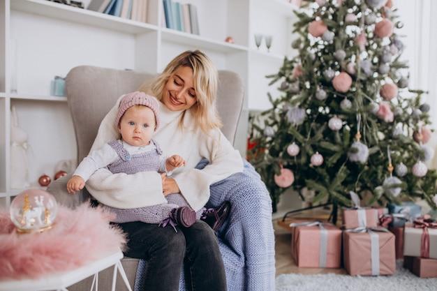 クリスマスツリーのそばの小さな娘を持つ母
