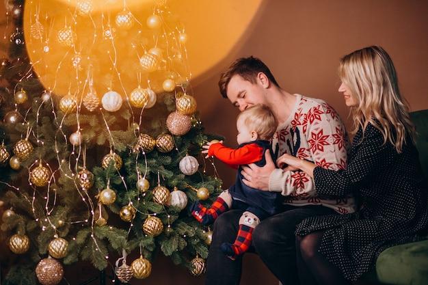 Молодая семья с девочкой, сидя у елки