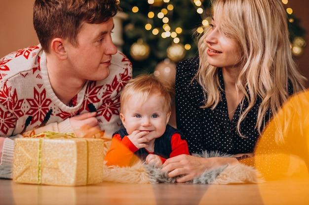 Молодая семья с маленькой дочерью держит рождественские подарки