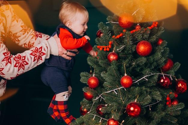 クリスマスツリーによって彼の赤ん坊の娘を持つ父