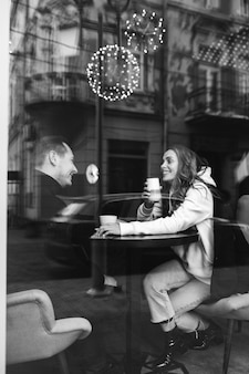 窓の後ろのカフェに座っている若いカップル