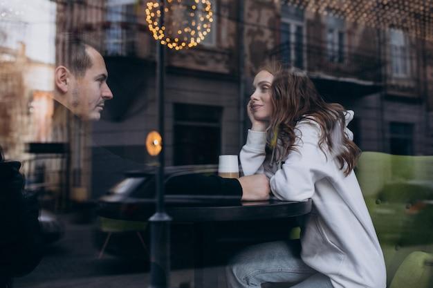 Молодая пара сидит в кафе за окном