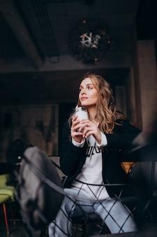 カフェの中の椅子に座っている若い女性