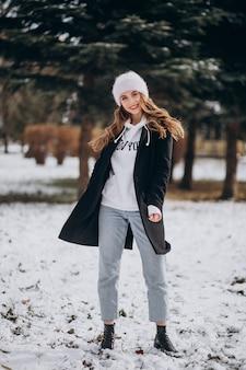 かわいい帽子の冬の公園で若い魅力的な女性
