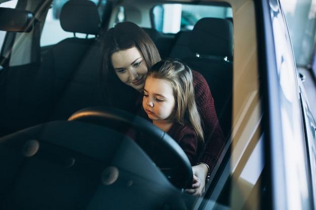 車の中に座っている小さな娘を持つ若い母親