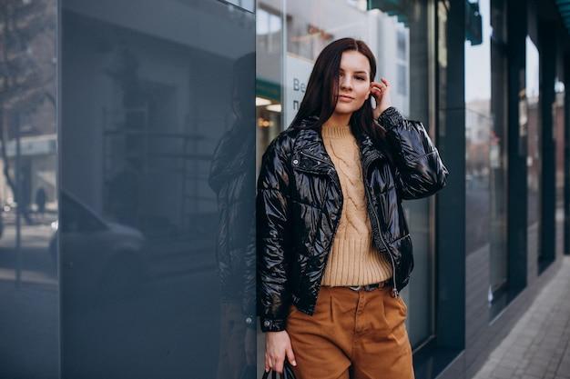 屋外の暖かいジャケットの若いきれいな女性