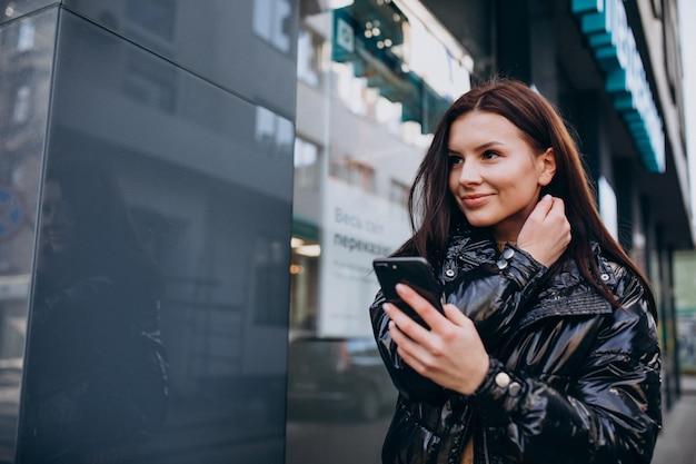 屋外の電話を使用して若い女性