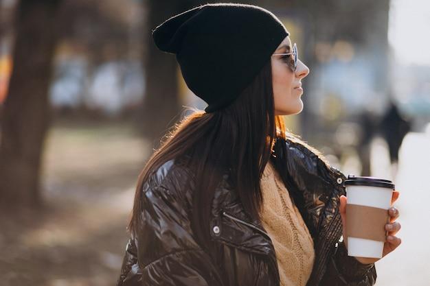 公園でコーヒーを飲む若い女性