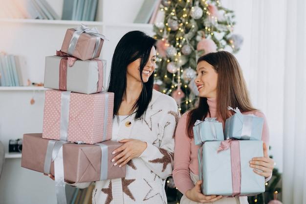 クリスマスと大人の娘を持つ母がクリスマスツリーでプレゼントします。