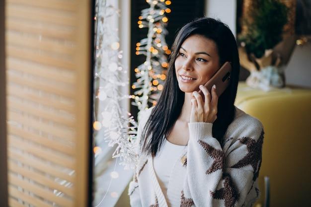 電話を使用して、窓のそばに立っている若い女性