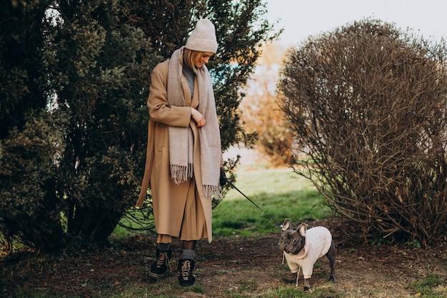 Красивая женщина с французским бульдогом гуляя в парк