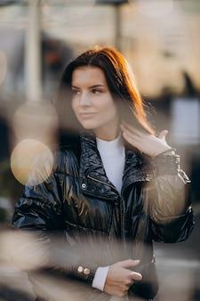 若い女性モデルが通りの外でポーズ
